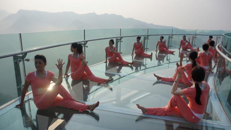 أشخاص يمارسون رياضة اليوغا على منصة من الزجاج عشية يوم اليوغا العالمي