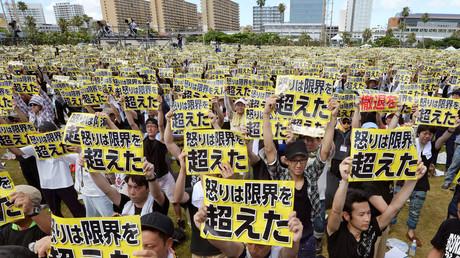 """مشاركون في تظاهرة جرت في أوكيناوا احتجاجا على الوجود العسكري الأمريكي في اليابان يرفون هتافات كتب عليها: """"الغضب تجاوز الحد"""""""