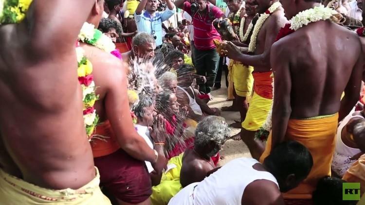 هنود يكسرون جوز الهند برؤوسهم كجزء من احتفال بوذي