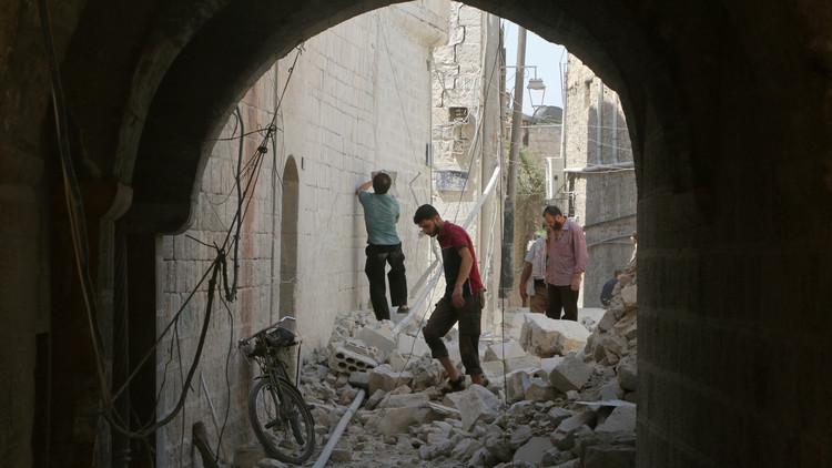 الناس يمشون بين أنقاض مبان مدمرة في حلب القديمة