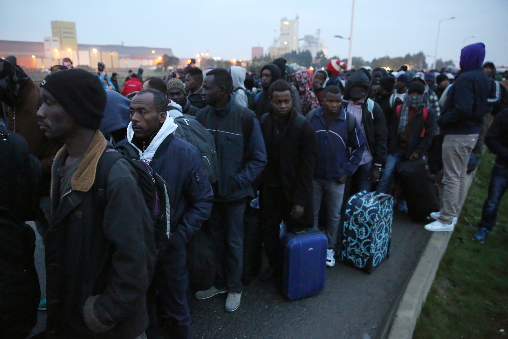 مهاجرون يقفون في انتظار نقلهم من مخيم كاليه إلى مراكز الإيواء الشرعية