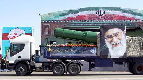 شاحنة إيرانية تحمل صاروخا وصورة لآية الله علي خامنئي