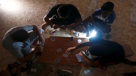 أرشيف - ليبيون يلعبون الورق في ظل انقطاع التيار الكهربائي، بنغازي - ليبيا