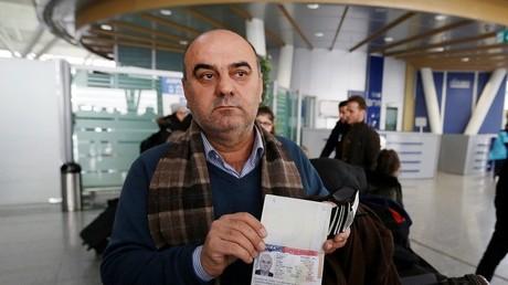 احد المسافرين العائدين من مصر، العراقي فؤاد سليمان يعرض الفيزا الأمريكية