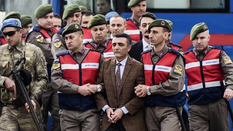رجال الأمن يقودون أحد المتهمين في قضية محاولة اغتيال أردوغان إلى قاعة المحكمة