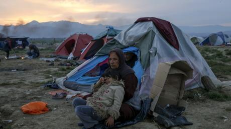 لاجئة مع طفلتها في مخيم على الحدود اليونانية المقدونية