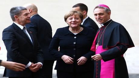 رئيس أساقفة الفاتيكان جورج جانزوين يستقبل ميركل وزوجها يواكيم ساوير أثناء وصولهما للاجتماع مع البابا فرانسيس في الفاتيكان في 24 مارس 2017