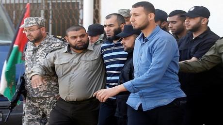 قوات حركة حماس برفقة مدان بقتل مازن فقهاء، وهو يغادر محكمة عسكرية تديرها حماس في مدينة غزة في 21 مايو 2017