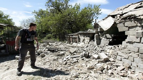 موظف من البعثة الأوروبية في أوكرانيا يعاين منزلا تعرض للقصف في دونباس، 13 مايو 2017