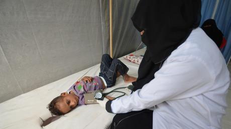 ممرضة تفحص طفلا مصابا بمرض الكوليرا في مستشفى البحر الأحمر في مدينة الحديدة اليمنية.