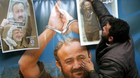 شاب يقف أمام ملصق للإضراب يصور المعتقل مروان البرغوثي