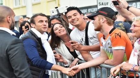 الرئيس الفرنسي إيمانويل ماكرون مع ناخبية في مدينة توكي، شمال فرنسا، حيث سيدلي بصوته في الاقتراع الأحد 11 يونيو