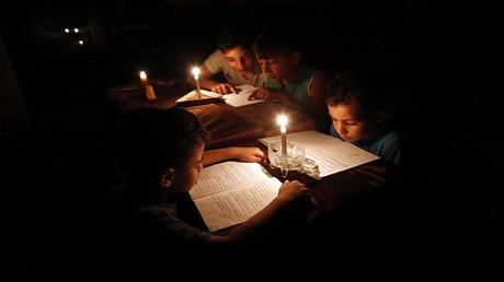 أطفال في قطاع غزة يقرأون الكتب على ضوء الشموع وسط انقطاع كهرباء