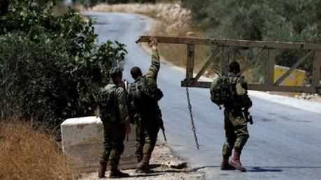 جنود اسرائيليون يقومون باغلاق أحد مداخل قرية دير أبو مشعل في الضفة الغربية