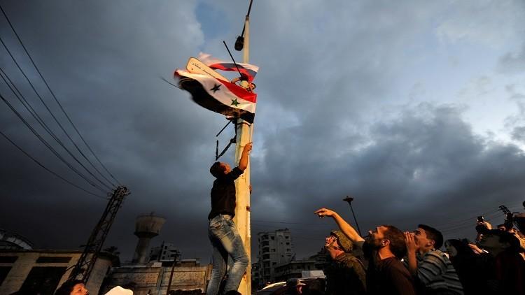 سوريون يرفعون العلم السوري في حي الوعر بحمص بعد خروج المسلحين