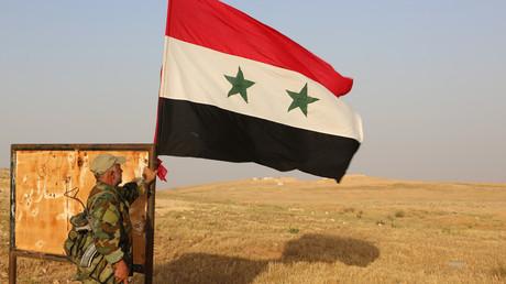 عنصر من الجيش السوري بنصب علم سوريا