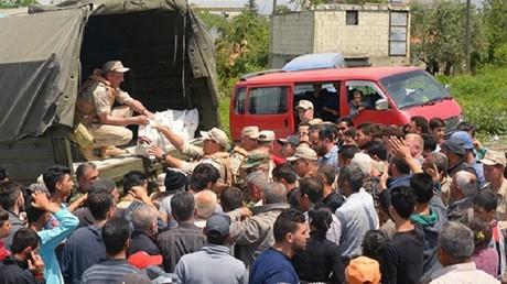 صورة من الأرشيف لجنود روس يوزعون المساعدات على محتاجيها في سوريا