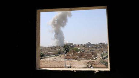 عمود دخان يتصاعد فوق أحد أحياء الرقة