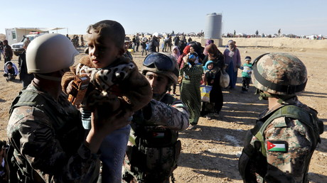 جنود أردنيون يساعدون لاجئين سوريين