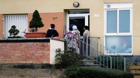زوار على باب منزل عائلة اوكبير في ريبول حيث تحقق الشرطة في الاعتداءين اللذين أوقعا 14 قتيلا ونحو 120 جريحا في برشلونة