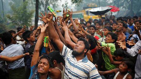 الروهينغا يحاولون التقاط ما يرمى لهم من مواد غذائية في بنغلاديش