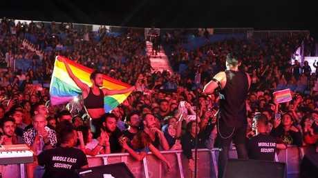 """أحد جماهير فرقة """"مشروع ليلى"""" اللبنانية المستقلة يمسك بعلم المثليين أثناء حفل الفرقة في مدينة إدهن بلبنان، 12 اغسطس 2017"""