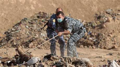 عناصر من الشرطة العراقية يسحبون رفات من تحت الأنقاض - أرشيف -