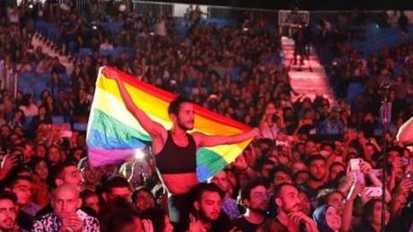 أحد الحضور يرفع راية قوس قزح (للمثليين) في حفل لفرقة موسيقية لبنانية