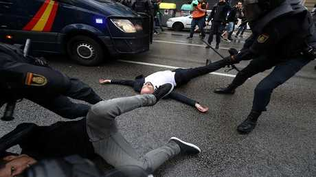 عنصر من قوات الأمن الإسبانية يسحب أحد المحتجين من قدمه