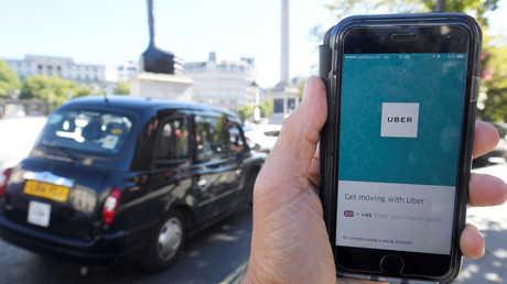 """شخص يستخدم تطبيق """"Uber"""" في لندن"""