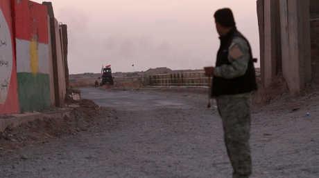 أحد عناصر البيشمركة يراقب قوات من الحشد الشعبي جنوب كركوك
