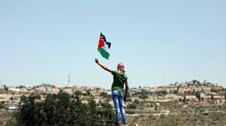 فلسطيني يرفع العلم الفلسطيني قبالة مستوطنة مقامة على أراضي قرية كفر قدوم قرب نابلس في الضفة