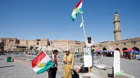 مواطنون في أربيل يمسكون أعلام كردستان العراق وصورة لرئيسها، مسعود بارزاني.