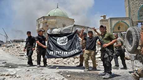 """أرشيف - جنود عراقيون يحملون راية """"داعش"""" بالمقلوب بعد تحرير مركز مدينة الموصل"""