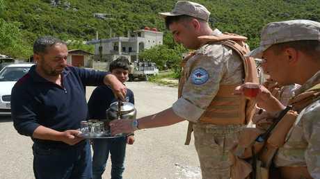 مواطن سوري يقدم الشاي لعسكريين من مركز المصالحة الروسي