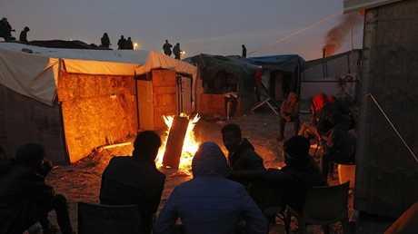 مهاجرون يجتمعون حول نار في مخيم كاليه الفرنسي - أرشيف