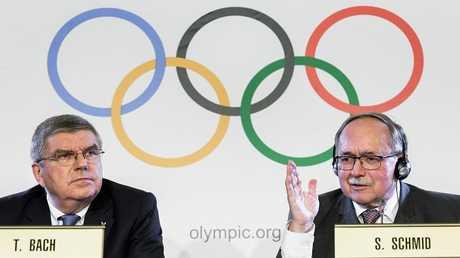 رئيس لجنة التحقيق التابعة للجنة الأولمبية الدولية صامويل شميد (اليمين)