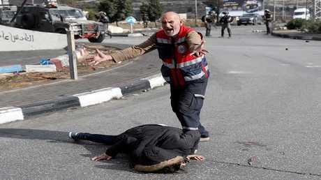 رجل اسعاف يصرخ قرب جثمان فلسطيني قتل برصاص الجيش الإسرائيلي