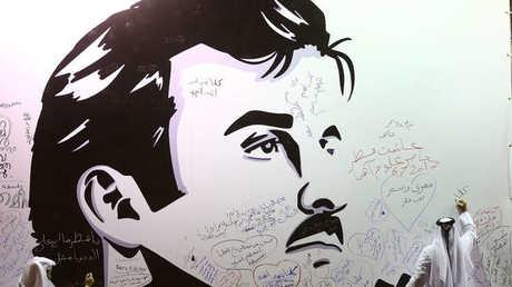 قطريون يكتبون تعليقات على جدار رسمت عليه صورة أمير قطر، الشيخ تميم بن حمد آل ثاني.