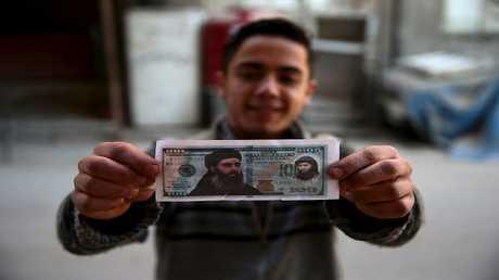 أرشيف - طفل يحمل قصاصة ورقية عليها صورة زعيم تنظيم داعش الإرهابي أبو بكر البغدادي، سوريا 27 ديسمبر 2015