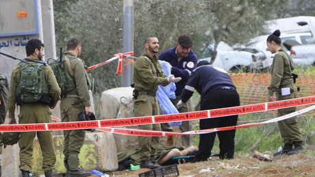 جنود إسرائيليون يحشدون حول جثة شاب فلسطيني قتيل