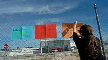 ناشطة إسبانية ترفع لافتات تندد باحتجاز المهاجرين في سجن أرخيدونا