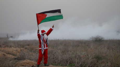 فلسطيني يرتدي ملابس بابا نويل خلال تظاهرة على حدود قطاع غزة