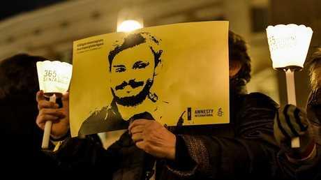 رجل يمسك صورة الباحث الإيطالي جوليو ريجيني خلال وقفة تضامنية في روما