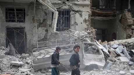 طفلان سوريان أمام أنقاض مباني مدمرة في الغوطة الشرقية