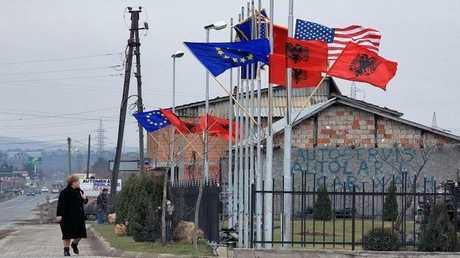 أعلام الولايات المتحدة والاتحاد الأوروبي وألبانيا على مبنى في كوسوفو