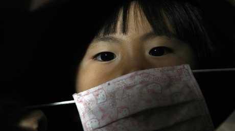 فتاة يابانية تضع كمامة للوقاية من الأمراض - أرشيف