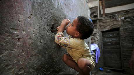 طفل يشرب الماء في أحد الأحياء الفقيرة بمنطقة الجيزة