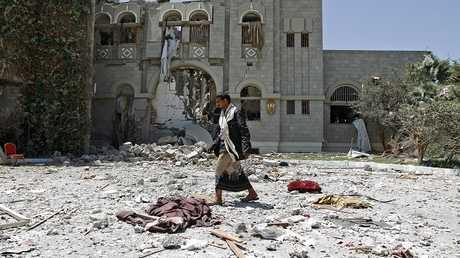 مواطن يمني يسير امام بيت مفجر في اليمن