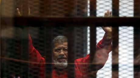 الرئيس المصري الأسبق محمد مرسي خلف القضبان في قاعة محكمة بالقاهرة،21 يونيو  2015